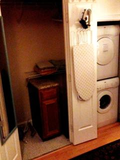 Washer/Dryer, iron and ironing board in bedroom area