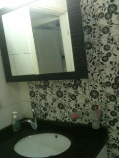 The bathroom washbasin and a mirror storage cabinet
