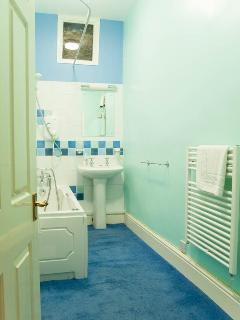 Bathroom with electric shower and bubbly spa bath for easing aching muscles after hill walks