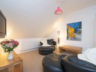 Open plan living with flat screen TV, home entertainment system, DVD's and books