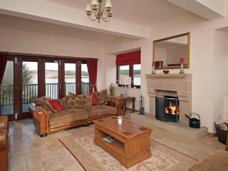 Main lounge with open fire and doors opening out onto decking