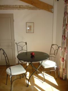 The dining area, with sunlight pouring in through the French windows