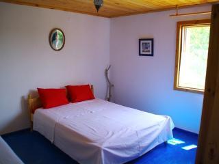 chambre bleue avec lit double et télé