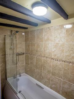 The bathroom comprises of a bath with overhead mixer shower, sink & underfloor electric heating