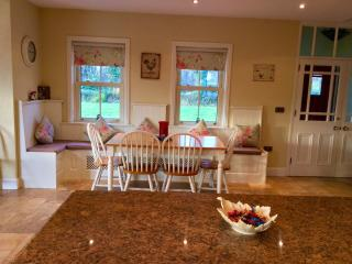 Window seat with kitchen table and chairs in open plan kitchen