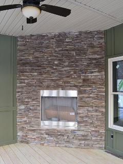 Stacked stone gas fireplace inside the screened in porch