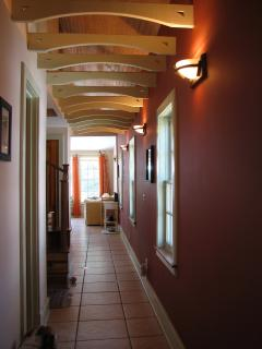 cool hallway we designed with a red accent wall looking towards pool living room