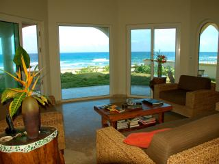 Downstairs living area with full ocean view and three sliding glass doors to access the beach