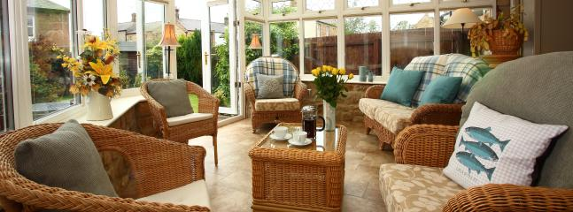 Spacious, sunny conservatory with wicker furniture and views onto the delightful enclosed garden