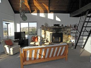 The fireplace makes the living room very cozy. It also has a high vaulted ceiling with a fan.