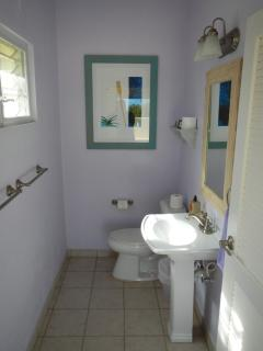 Powder room is located close the the pool deck and BBQ area.