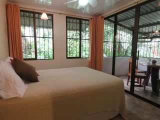 Master bedrrom with queen bed, A/C, opens to deck with view of garden and creek