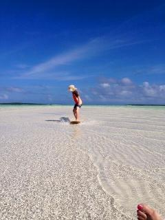 Skimboarding across the endless Exuma sandbars