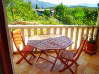 Balcony with relaxing view of green area, with table and chairs, where you can eat or simply rest