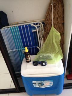 Beach chairs, beach umbrella and cooler.