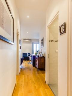 Interior hallway with contemporary, wooden floorboards leading to all rooms