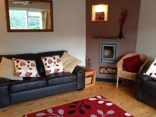 The lounge with comfy sofa and 7kW log burner opposite the large picture window.