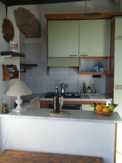 kitchenette with stove, oven, refrigerator, lemon squeezer, moka and all the kitchen utensils