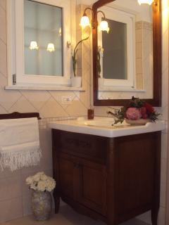 bagno con elegante mobile in legno e doccia di cristallo