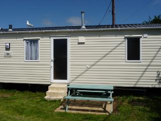 Sunny picnic table and large grass area at side of caravan