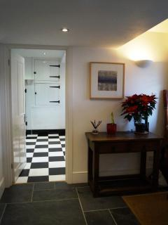 Entrance leading to utility room with 2 showers and hangers for wet wetsuits.