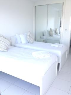 The spacious second bedroom with 2 single beds