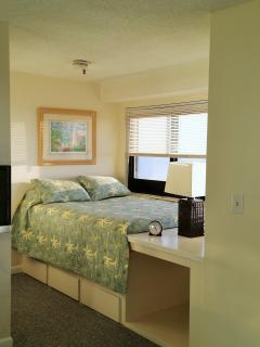 Bedroom with beachfront view, built in drawers under, and cubby space for luggage!