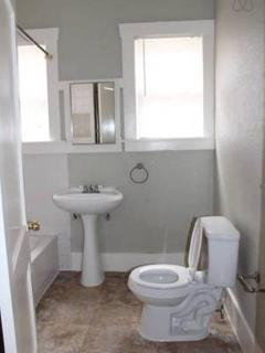 Small but efficient bathroom with full sized tub, blow dryer, and fresh towels.