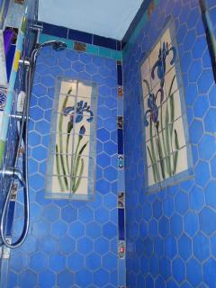 Local artisan hand-crafted the Iris tiles for this shower!