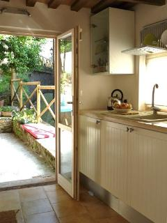 Galley kitchen leading to patio and garden