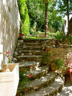 Wall fountain on patio and steps leading to garden