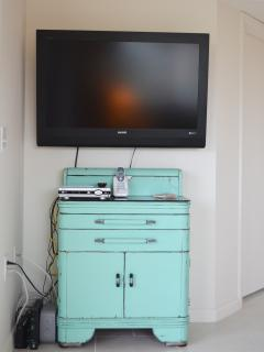 Large screen tv mixed with fun and unique furniture.