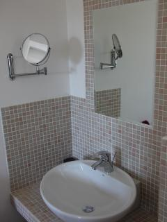 The Shower room in Les Cerisiers has attractive mosaic wall tiling