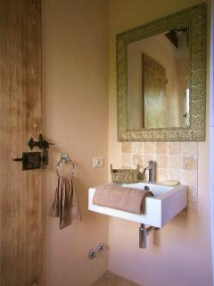 Basin and mirror in a bathroom ensuite with bidet, shower and loo.