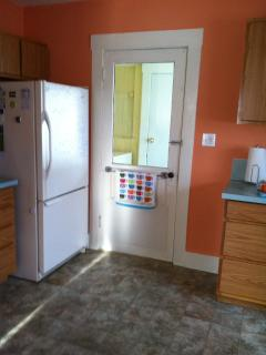 Full sized fridge and door to the laundry area