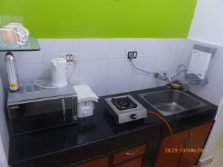 The kitchen with a gas stove, microwave, water purifier, fridge and utensils