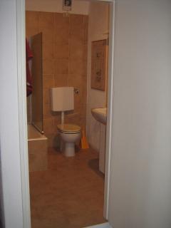 Bathroom ajourning 2nd bedroom. Bath/shower, WC, wash basin, cupboards and mirror.