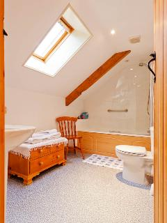 Adjoining bathroom with bath and overhead shower
