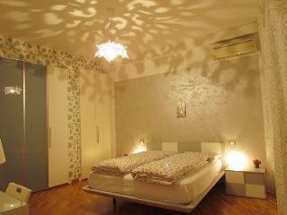 Camera da letto con armadio, comodini, televisore, poltroncina, tavolinetto