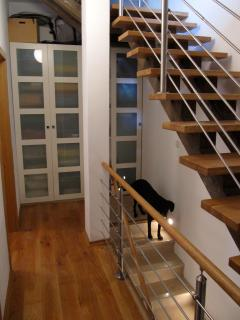 Linen cabinet in hallway on second level, oak stairs leading up to top floor