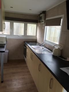 Fully fitted kitchen with full size cooke, microwave, integrated fridge with freezer compartment.