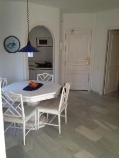 Dining area beside the kitchenette, main door straight ahead and master bedroom.