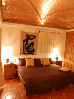 Master bedroom at night with view of vaulted ceiling