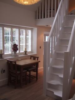 Dining area overlooking garden, paddle stairs to mezzanine bedroom