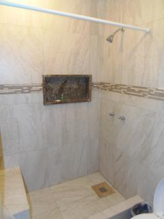 Full size shower with bench seat.