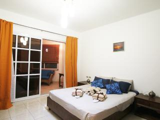 Master bedroom with large double wardrobe containing safe, leading to balcony view to Ali Babe pool