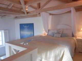 The raised bedroom area of the open plan, split level villa with views of across the sea