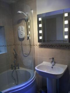 Newly refurbished bathroom with lighting on.