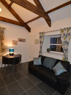 The living area has exposed beams into the roof space and has a double sofa-bed.