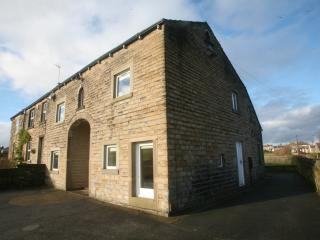 Front and side of Marsh Royd Barn with parking spaces for 5 cars